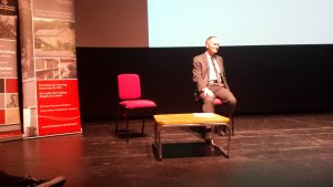 Andrew Green seated on stage at Taliesin, taking questions from the audience